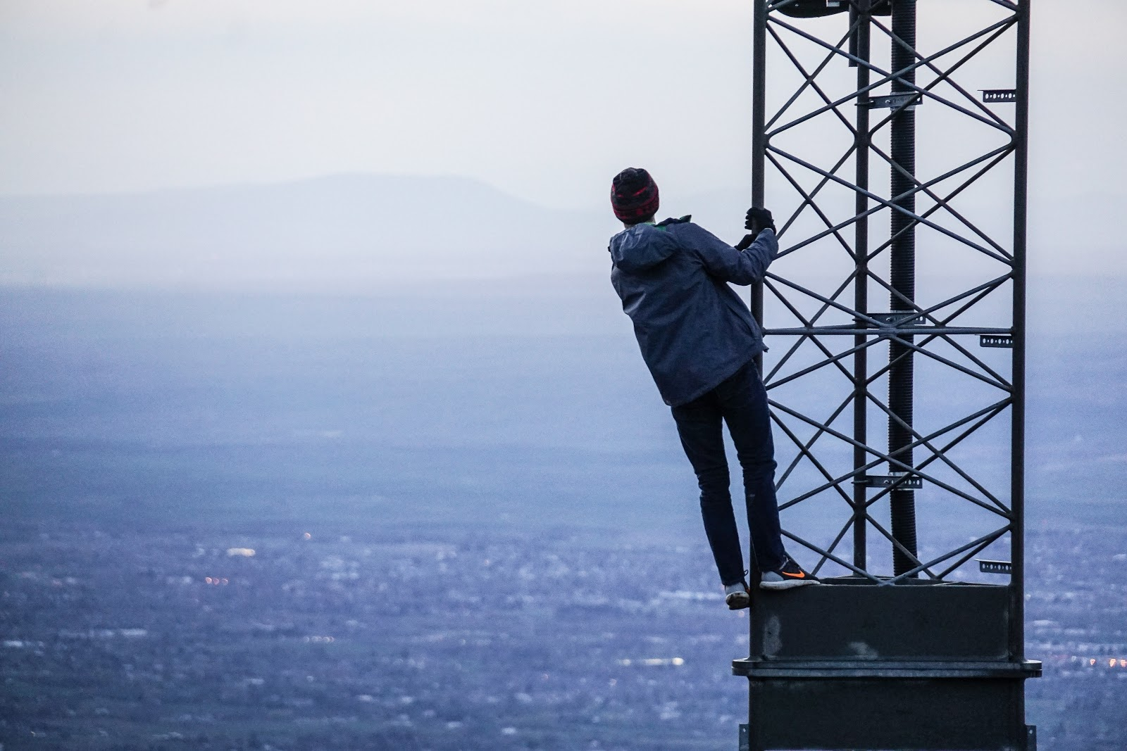 man on cell tower overlooking city dangerous